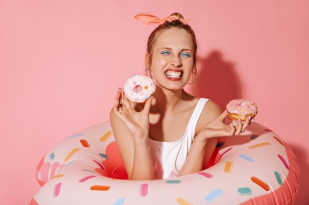 Emotionales mädchen mit ohrringen und stilvollem make-up im leichten badeanzug, der zwei donuts hält und mit rosa großen schwimmringen an isolierter wand posiert