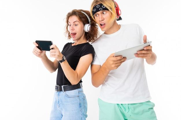 Emotionales mädchen spielt ein spiel am telefon und der mann mit dem tablet in den händen guckt auf den bildschirm des mädchens an einer weißen wand
