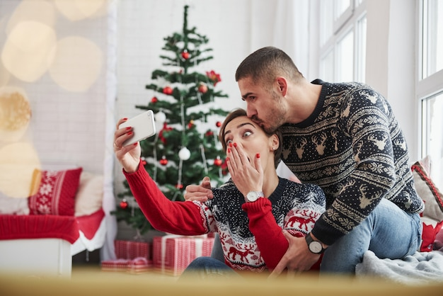 Emotionales mädchen wünschen lustiges foto. glückliche junge leute sitzen auf der fensterbank im raum mit weihnachtsdekorationen