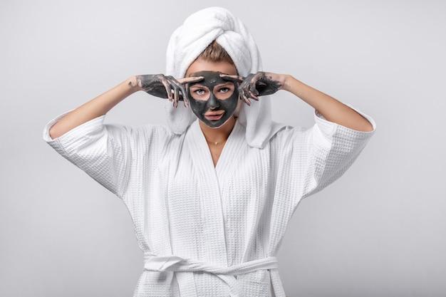 Emotionales modell posiert in einem weißen bademantel mit einem handtuch auf dem kopf