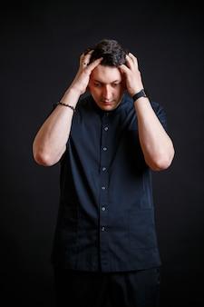 Emotionales nahaufnahmeporträt eines jungen männlichen arztes in medizinischer kleidung. auf schwarzem hintergrund isoliert