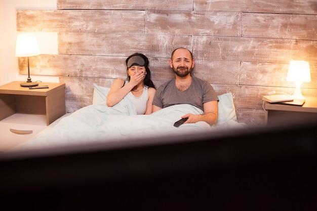 Emotionales paar im pyjama beim ansehen eines films im fernsehen.