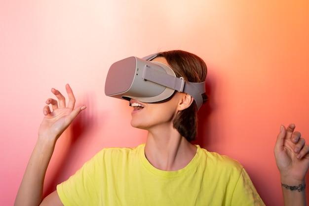 Emotionales porträt der frau in der brille der virtuellen realität im studio auf rosa orange hintergrund