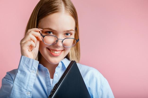 Emotionales porträt einer lächelnden jungen frau mit brille mit laptop isoliert über rosafarbenem hintergrund