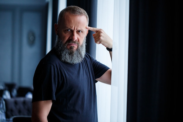 Emotionales porträt eines erwachsenen grauhaarigen mannes mit bart in einem schwarzen t-shirt
