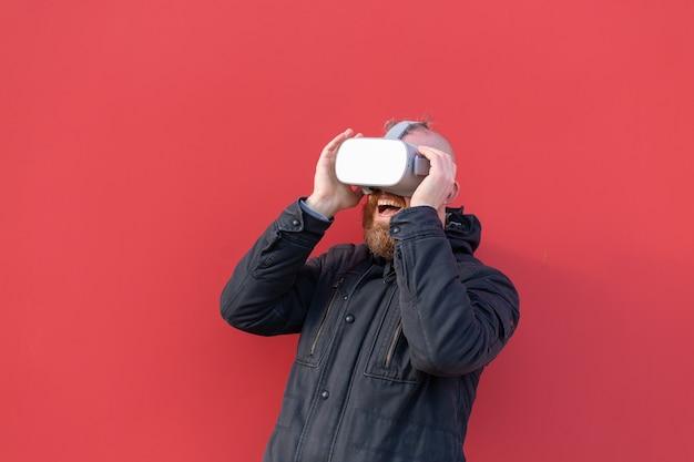 Emotionales porträt eines mannes auf der straße, der realitätsbrille gegen den hintergrund einer roten wand trägt