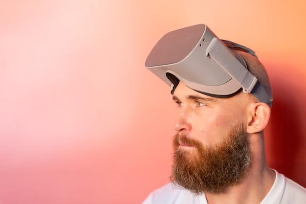 Emotionales porträt eines mannes mit einem bart, der eine brille der virtuellen realität im studio auf einem rosa orange hintergrund trägt
