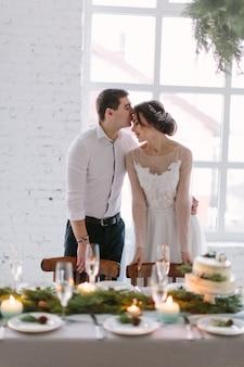 Emotionales schönes brautpaar, das beim hochzeitsempfang im weißen saal mit hochzeitsdekorationen lächelt, küsst und umarmt