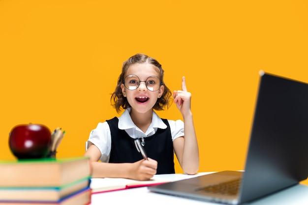 Emotionales schulmädchen hebt den finger hoch sitzend mit laptop im brillenfernunterricht