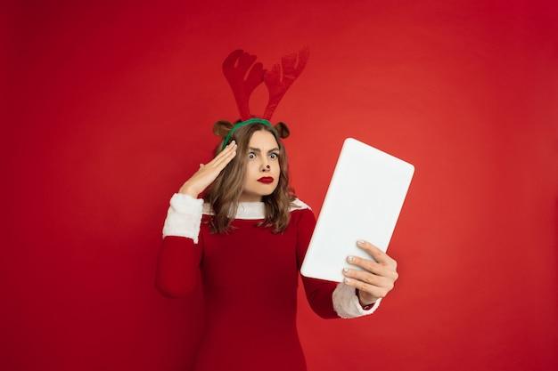 Emotionales scroll-tablet. konzept von weihnachten, neujahr 2021, winterstimmung, feiertage. schöne kaukasische frau mit langen haaren wie santa's rentier anziehende geschenkbox.
