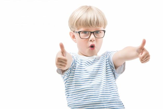 Emotionales süßes kind zeigt ok oder daumen hoch. entzückendes kind auf lokalisiertem hintergrund. studioaufnahme des schülers.