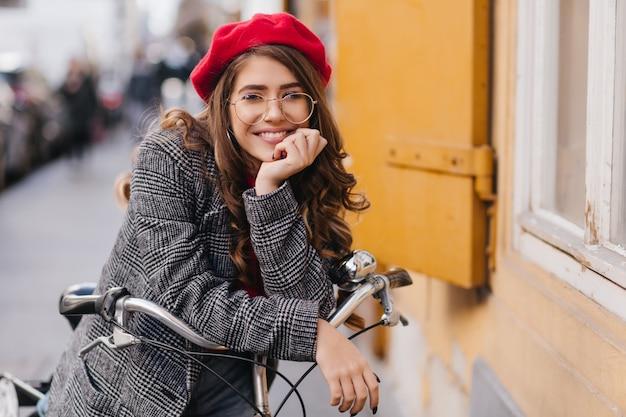 Emotionales süßes mädchen mit verträumter lockiger frisur, die auf fahrrad aufwirft