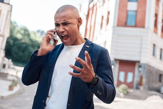 Emotionales telefongespräch junger mann, der auf die straße der stadt geht und wütend auf dem smartphone schreit