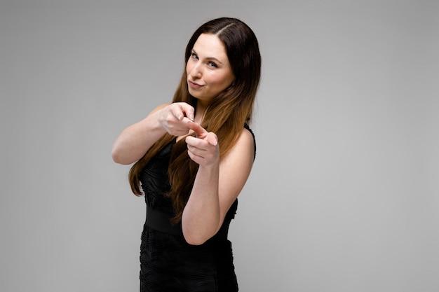 Emotionales überzeugtes plusgrößenmodell, das im studio zeigt finger auf kamera auf grauem hintergrund steht