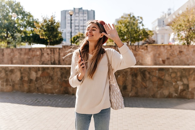 Emotionales weibliches modell in der baskenmütze, die hand auf stadthintergrund winkt. fröhliche, gut gekleidete dame, die im herbsttag im freien chillt.