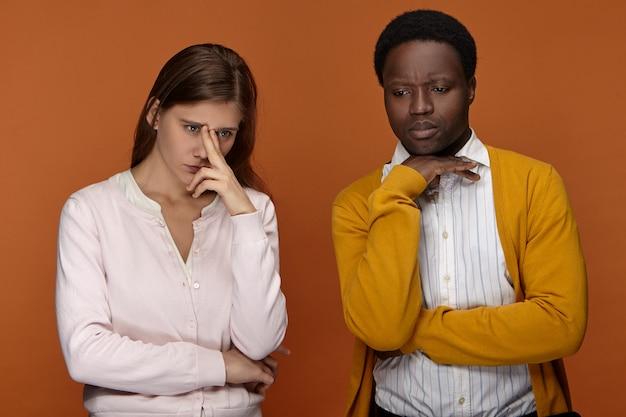 Emotionen, gefühle und reaktionen. bild eines stilvollen jungen interrassischen paares, das unbehaglich frustriert aussieht, sich sorgen um sein vermisstes kind macht, nervös ist und nicht miteinander spricht