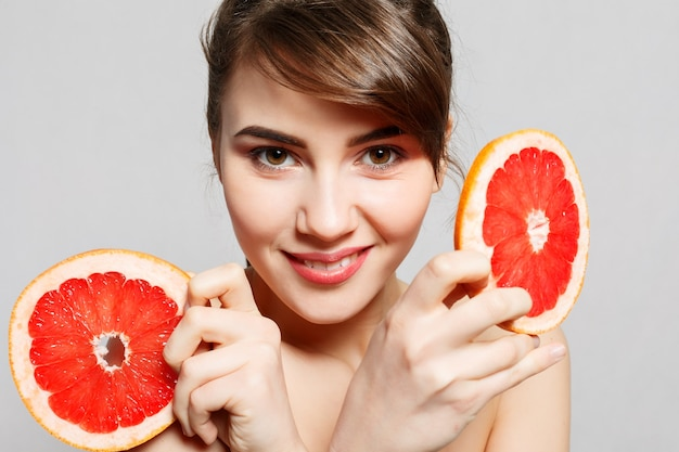 Emotionen, gesundheit, menschen, essen und schönheitskonzept - schönheitsporträt einer glücklichen frau, die eine grapefruit, emotionales porträt hält. mädchen lächeln