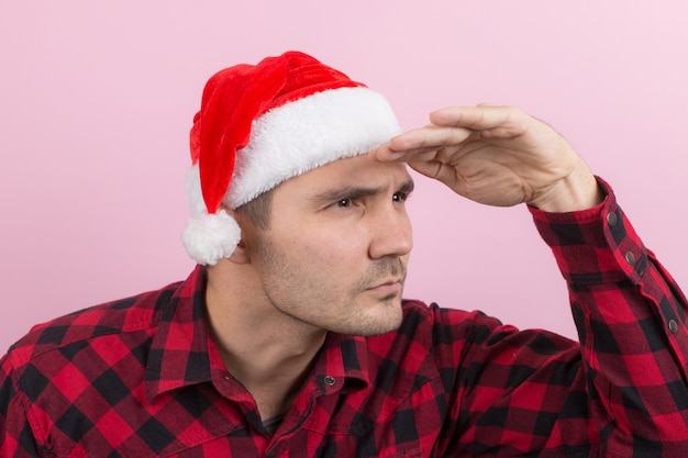 Emotionen im gesicht, wütend, böse, bandit, verschwörung. ein mann in einem karierten kaninchen und einem weihnachtlichen roten hut