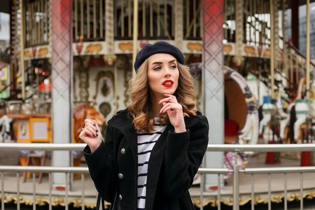 Emotionen, menschen, schönheit und lifestyle-konzept - mädchen französin, gegen ein karussell. straßenfoto der jungen frau, die stilvolle klassische kleidung trägt. weibliches modekonzept. französische art.
