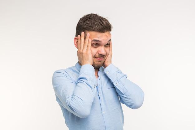 Emotions-, gesundheits- und menschenkonzept. gutaussehender mann, der an etwas denkt und kopfschmerzen auf weiß hat.