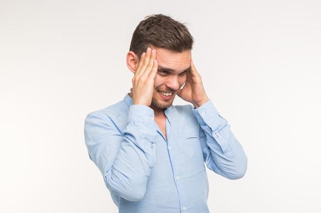 Emotions-, gesundheits- und personenkonzept - gutaussehender mann, der über etwas nachdenkt und kopfschmerzen auf weißer oberfläche hat