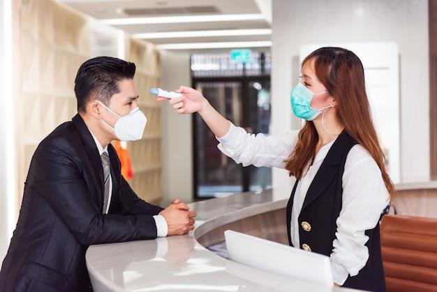 Empfangsbediener überprüft fieber mit einem digitalen thermometer auf fieberscan und schützt vor coronavirus