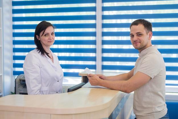 Empfangsdame der mittleren erwachsenen frau, die karte vom patienten in der zahnarztklinik erhält