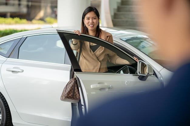 Empfangsdame, die eine asiatische kundenfrau begrüßt, um wartungsservice-mitte für die prüfung des autos im ausstellungsraum zu besuchen
