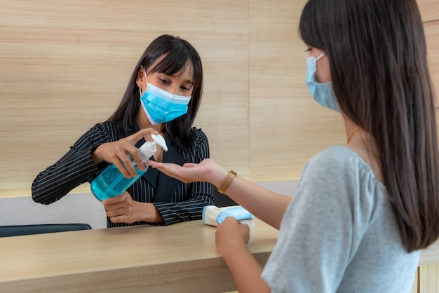 Empfangsdame und gast tragen gesichtsmaske an der rezeption während eines gesprächs im büro oder im krankenhaus