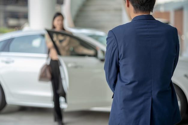 Empfangsdame, welche die asiatische kundenfrau begrüßt