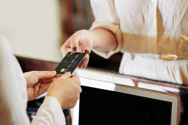 Empfangsmitarbeiter, der kreditkarte zurückgibt