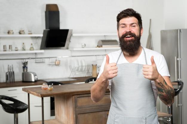 Empfehle schönes rezept. kulinarisches geschäft. brutaler selbstbewusster koch im restaurant. hipster bärtiger männlicher koch, der essen in der küche kocht. küche für echte männer. leckeres essen zu hause kochen. essen zu hause.