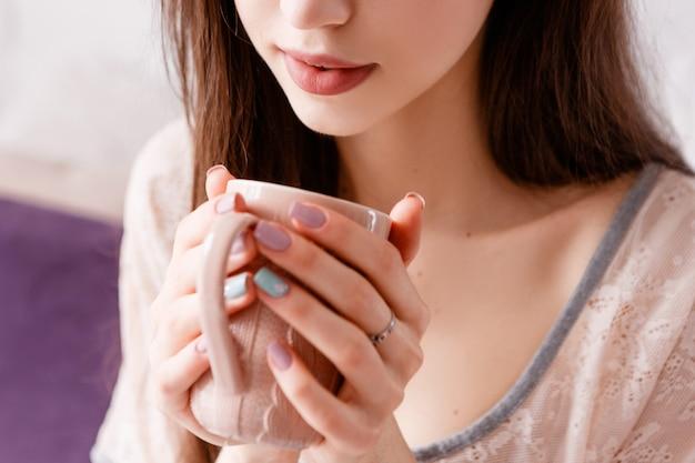 Empfindliche junge unerkennbare frau erfreut ihren morgenkaffee.