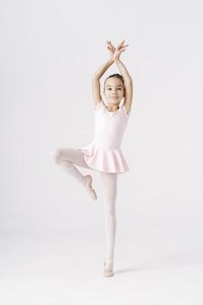 Empfindliche mädchenballerina, die in der balletthaltung auf weiß steht. arten persönlichkeitsentwicklungskonzept.