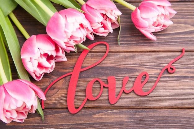 Empfindliche rosa tulpen auf einem braunen hölzernen hintergrund. nahansicht. blumenzusammensetzung. valentinstag
