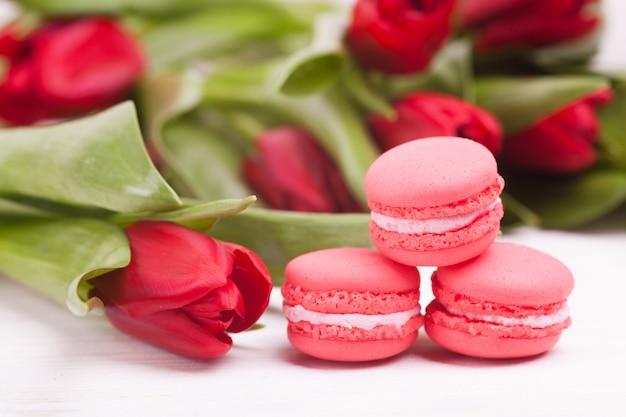 Empfindliche rote tulpen und macarons auf hölzernem. nahansicht. blumenzusammensetzung. blumenfrühling. valentinstag, ostern, muttertag.