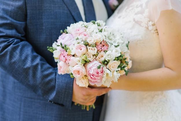 Empfindlicher blumenstrauß der braut in den händen der braut und des bräutigams, nahaufnahme