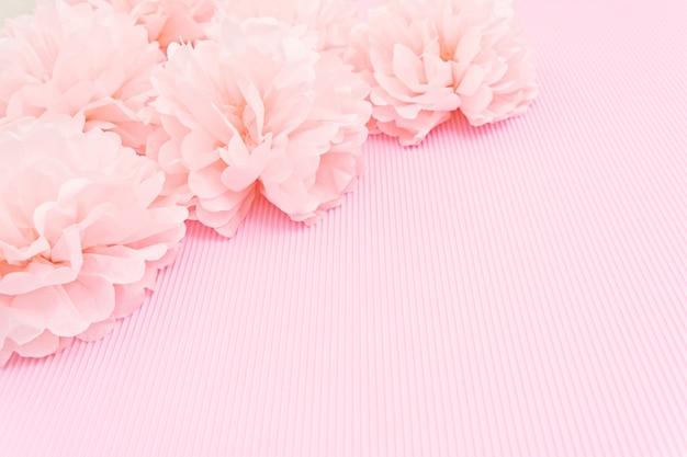 Empfindlicher rosa hintergrundspott oben mit papierpfingstrosen und platz für text.