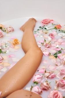 Empfindliches porträt einer erwartenden frau. schöne schwangere frau liegt in einem bad voller rosa blumen und milch