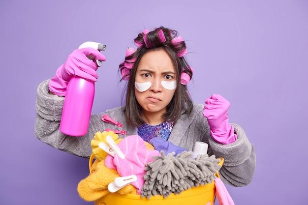 Empörte asiatische hausfrau ballt fäuste, die wütend auf jemanden ist, ballt die faust, hält eine waschmittelflasche, trägt flecken unter den augen auf lockenwickler posiert in der nähe eines beckens mit schmutziger kleidung, isoliert auf lila wand