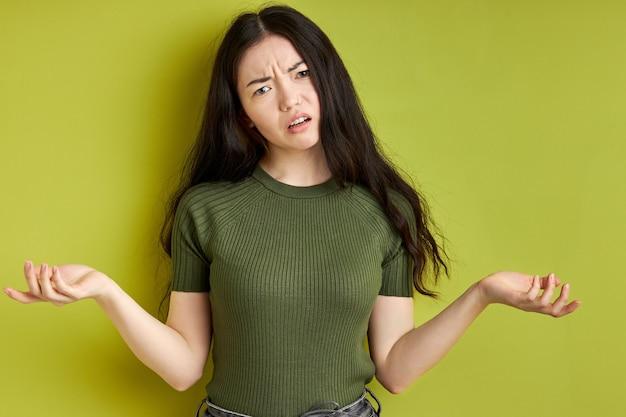 Empörte frau, die missverständnisse ausdrückt, hat negative emotionen isoliert über grünem hintergrund, menschliches emotionskonzept der leute