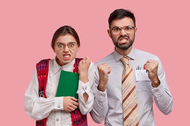 Empörte frau und mann mit genervten gesichtsausdrücken, geballten fäusten und zähnen, irritiert über viel arbeit, tragen elegante kleidung, stimmen nicht mit dem chef überein, isoliert auf rosa wand. negative gefühle