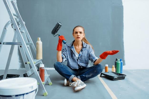 Empörte malerin mit farbroller, die nach der arbeit auf dem boden sitzt.