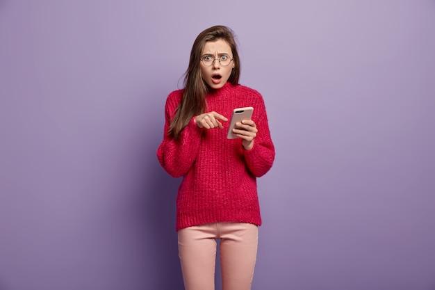 Empörte schockierte junge frau zeigt auf handy, zeigt etwas erstaunliches, überrascht von der empfangenen nachricht, trägt einen roten langarmpullover, hat einen verblüfften gesichtsausdruck und ist mit wlan verbunden