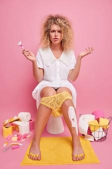 Empörte unzufriedene junge frau breitet handflächen aus, hält rasiermesser rasiert die beine und hat es eilig, da kurz vor dem date auf der toilettenschüssel posiert, trägt weißes kleid gelbe spitzenhöschen auf die beine gezogen
