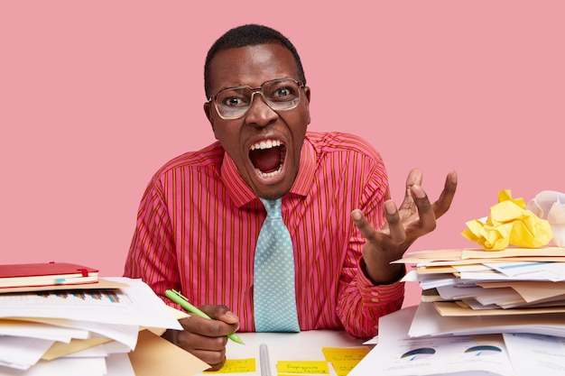Empörter geschäftsmann mit schwarzer haut schreit wütend, hält die hand erhoben, trägt ein formelles hemd und schreibt informationen in den notizblock
