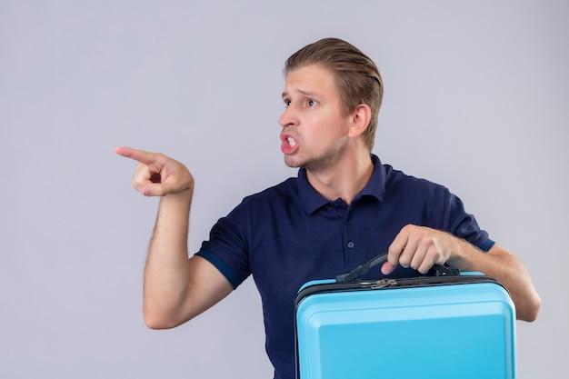 Empörter junger hübscher reisender mann, der koffer hält, der finger zu jemandem zeigt, der stehend argumentiert
