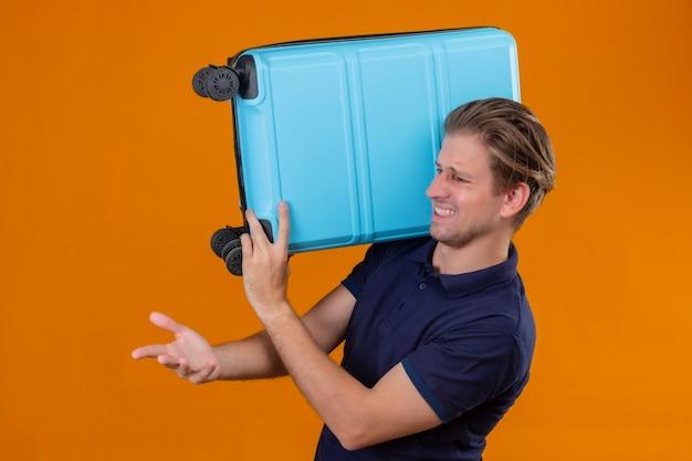 Empörter junger hübscher reisender mann, der koffer hält hände hebend fragt und stehend argumentiert