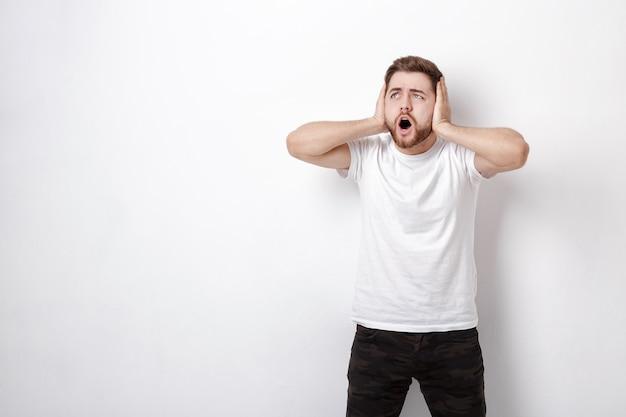 Empörter junger mann mit dunklen haaren und bart im weißen t-shirt schreit vor einer weißen wand