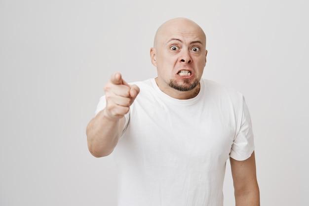 Empörter kahlköpfiger mann mittleren alters, der den finger beschuldigt